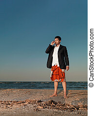 confident businessman smoking cigar on sea shore -...