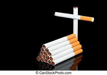 cigarettes coffin and cross over black background.