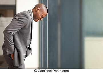 stressed african american businessman bang hi head against...