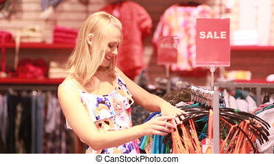 Sales section - Lovely blonde girl approaching the rack with...