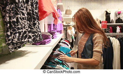 Particular about clothes - Glamorous young woman carefully...