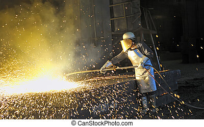 worker using torch cutter to cut through metal
