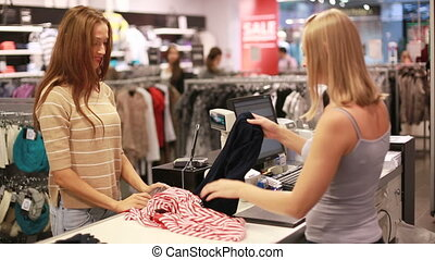 Checkout service - Lovely girl paying for her garments by...