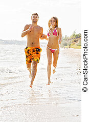 Young couple running along the beach