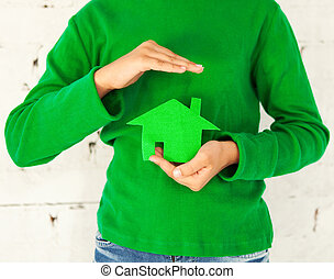 Little girl holding green house in hands. Concept