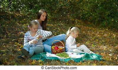 Family Having Picnic In The Park - Mother and two daughters...
