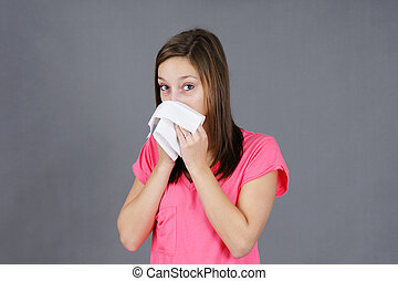 Young woman with colf or flu - Young woman blowing her nose...