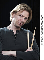 Man with drum sticks - Man in front of a black background an...