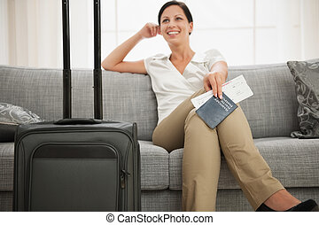 Dreaming woman with passport and air ticket sitting on couch