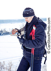 Young male skier drink hot tea