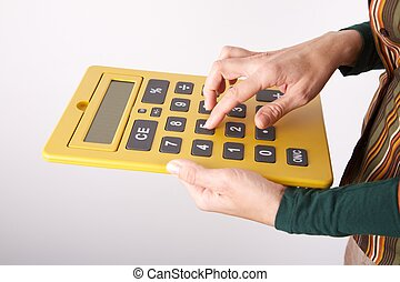 typing on big yellow calculator