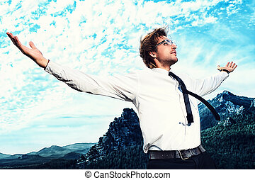 world business - Successful business man standing on a peak...