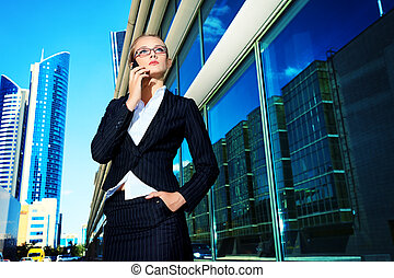 phone - Young business woman talking on her mobile phone in...