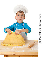 Little boy kneading the dough - Surprised little boy...