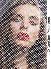 portrait of girl behind net she is in front of the camera