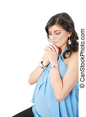 Hispanic pregnant woman praying with hands together