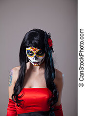 Young woman with sugar skull Halloween make-up wearing red...