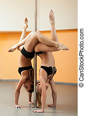 two athletic girl stand on hands during pole dance