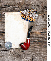 pipe, old paper, compass and model classic boat on wood...
