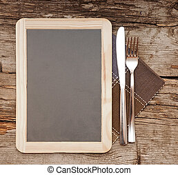 Menu blackboard lying on old wooden table with knife and...