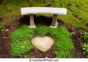 Heart Stone Bench - A beautiful stone bench sits next to...