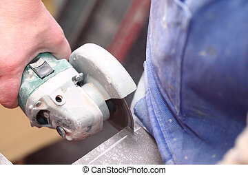 grinder worker cuts a stone the electric tool worker is...