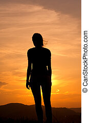 Silhouette of the woman in the mountains at sunset