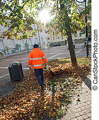 Street Sweeper with orange jacket while blowing the dried...