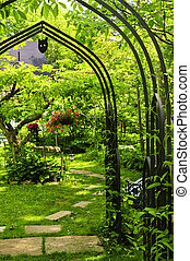 Lush green garden with wrought iron arbor