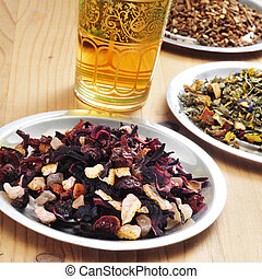 herbal tea - some plates with different dry leaves and...