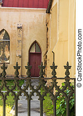 Wrought Iron Fence Before Red Church Door - An old brown...