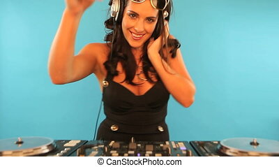 Beautiful brunette disc jockey wearing headphones standing...
