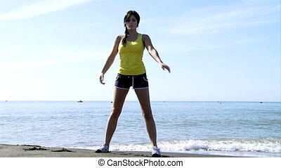 woman in front of ocean stretching - Gorgeous female model...