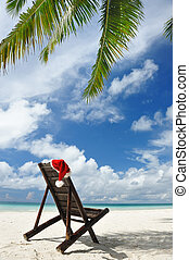 Tropical christmas - Santas hat and chaise lounge on the...