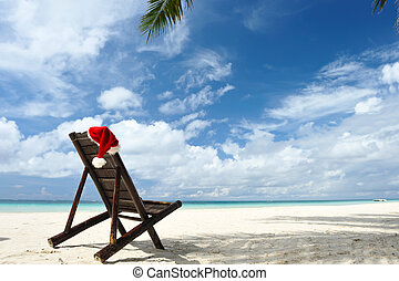 Tropical christmas - Santa's hat and chaise lounge on the...