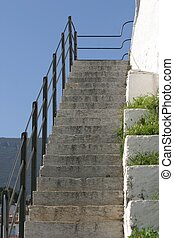 Old stone stairs with railing and white wall