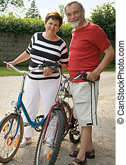 bicycling - An attractive senior couple bicycling