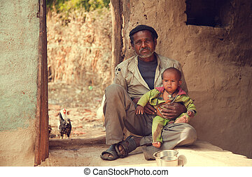 Indian poor father and son sitting on ground and he is...