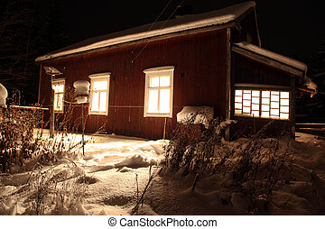 Classic Red wooden Finnish house in winter covered with snow...