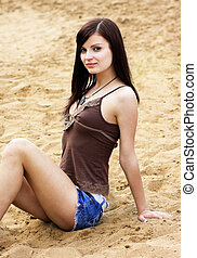Young beautiful girl sitting on sand