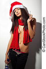 Sexy woman wearing red santa hat and holding a drink and a...