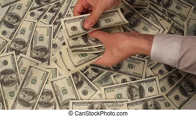 Hand counting money to a us banknote on dollars money...