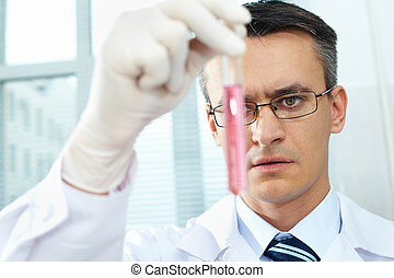 Chemist at work - Serious clinician gazing at flask with...