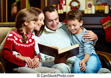 Family reading - Portrait of friendly family reading book on...