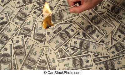Burning Money - Putting fire to a us banknote on dollars...