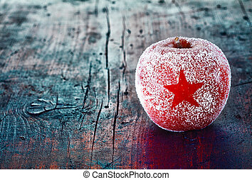 Frosted Christmas apple with a simple star decoration on an...