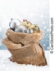 Winter Christmas baubles piled high in a rustic burlap bag...