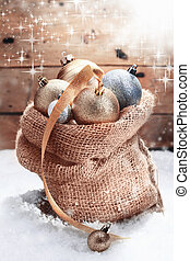 Decorative Christmas baubles piled high in a hessian bag on...