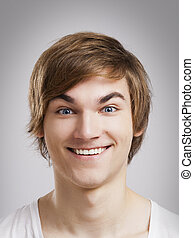 Happy face - Portrait of a handsome young man, over a gray...
