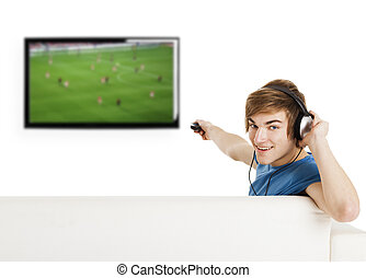 Watching football on TV - Young man sitting on the couch...